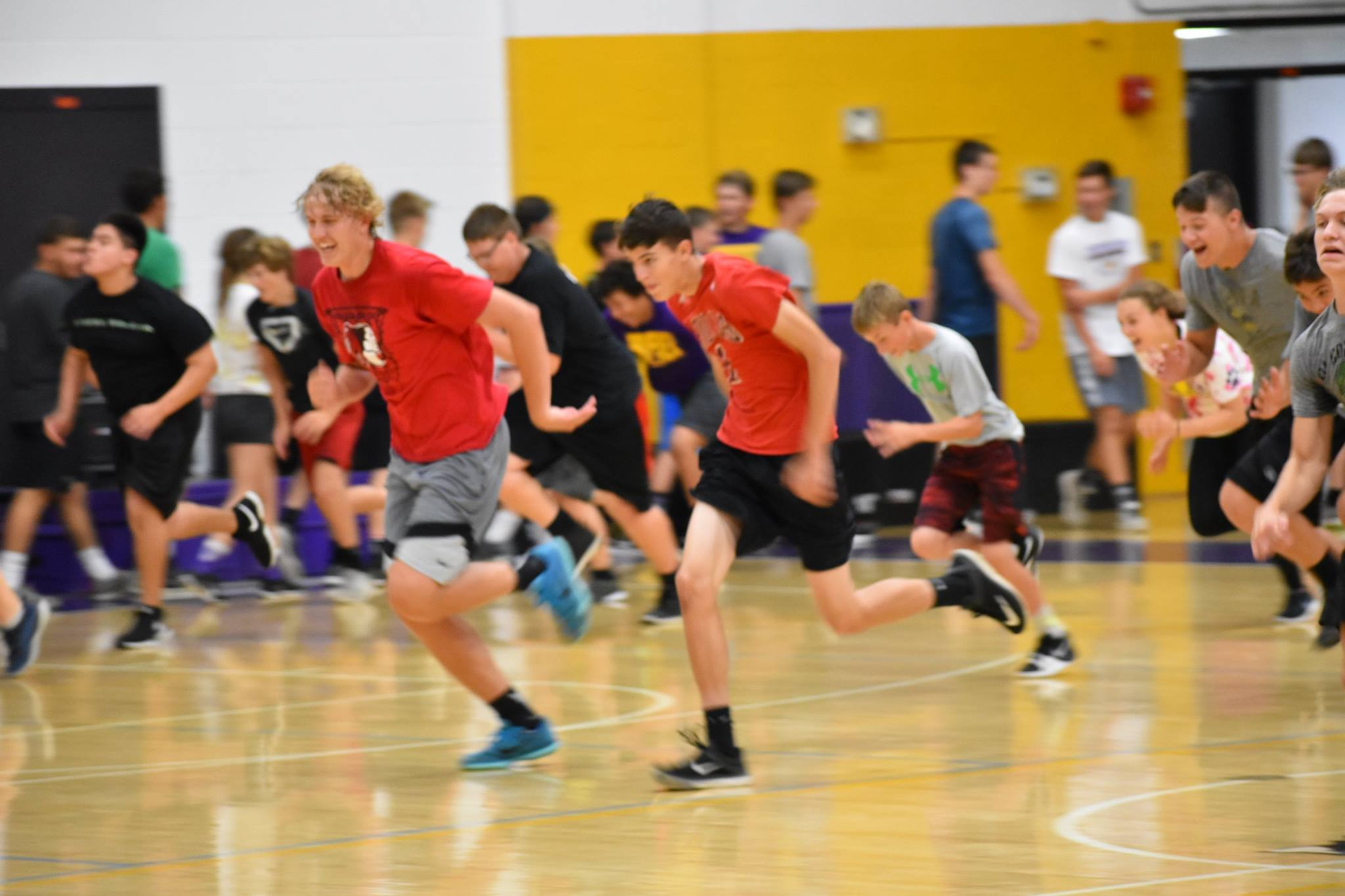 students running across the gym