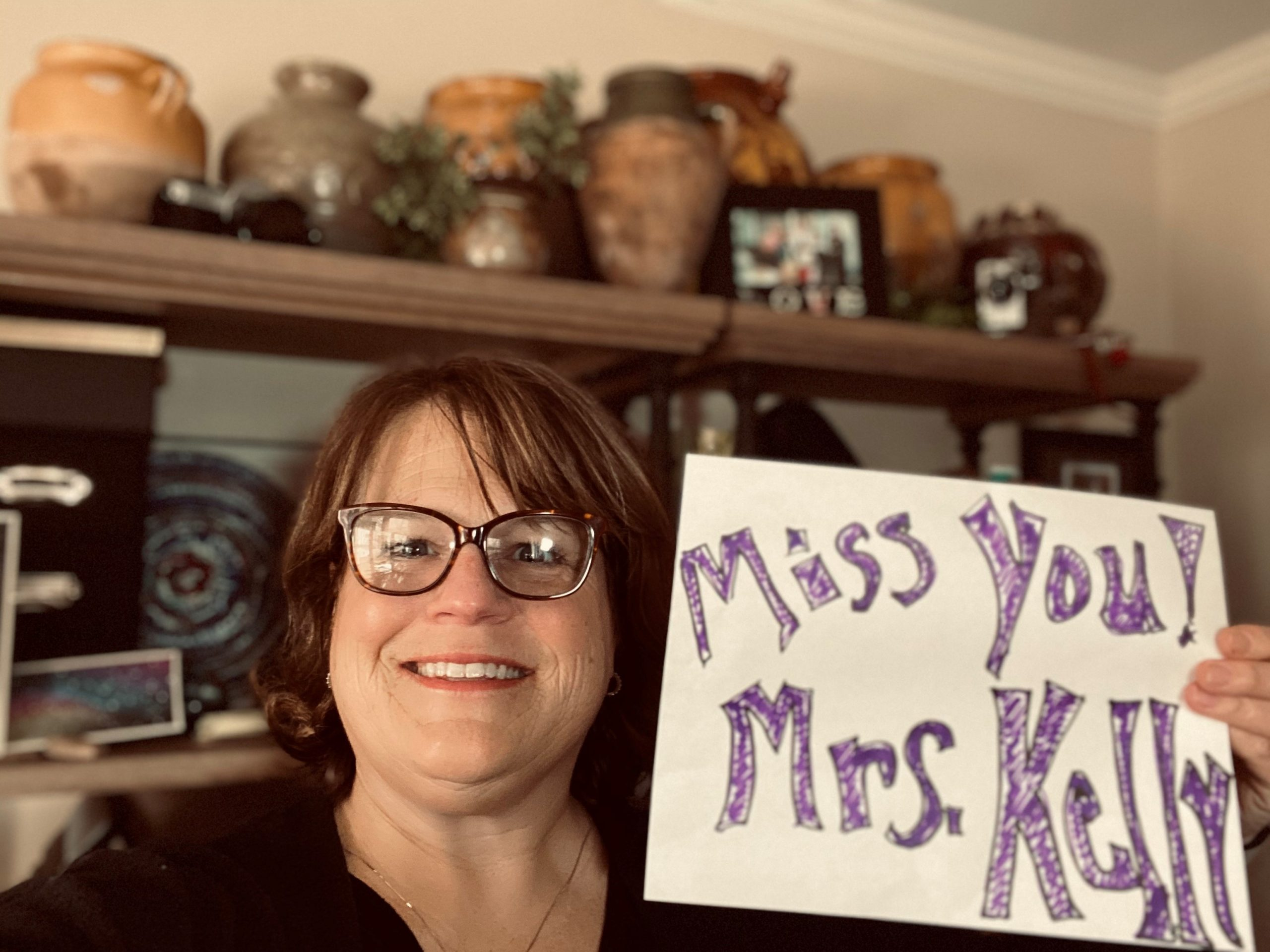 smiling teacher holding miss you sign