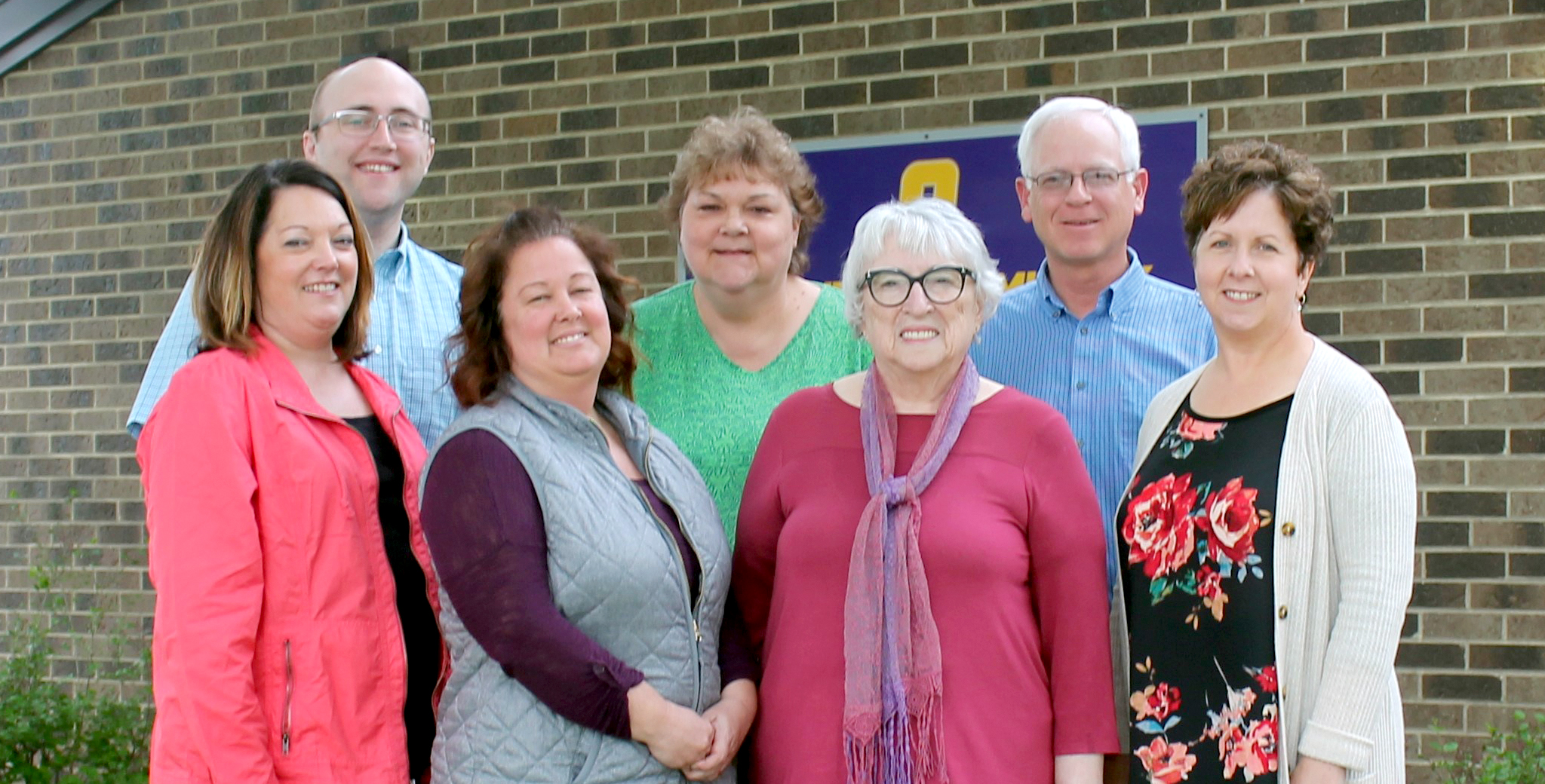 the Oelwein school board poses outside the central office building