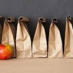 Many sack lunches with red and green apple